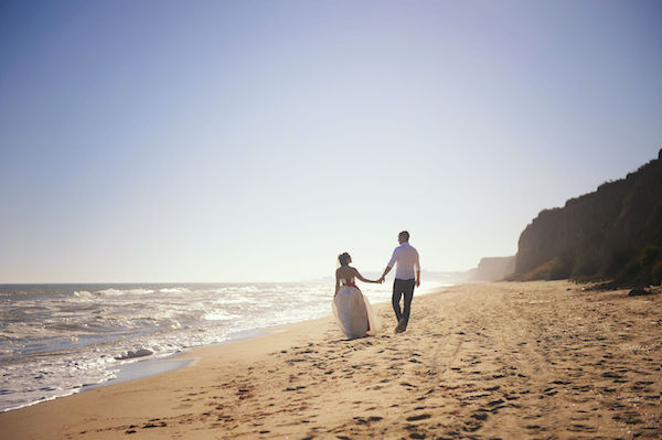 Romantic wedding couple celebrating marriage outdoors on a sea beach, smooth backlite